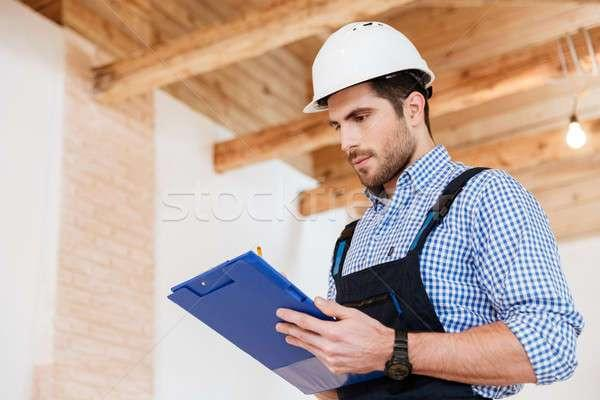 7104767_stock-photo-happy-builder-writing-notes-in-hardhat-with-clipboard